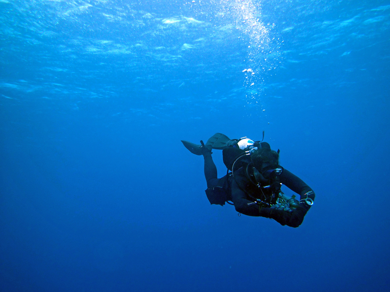 A scientist checks his dive computer on his safety stop while diving off the coast of Tutuila. After an hour or so on the reef conducting surveys, the scientists spend 3 minutes in about 15 feet of water so that they can off-gas. (Photo: NOAA Fisheries/Evan Barba)
