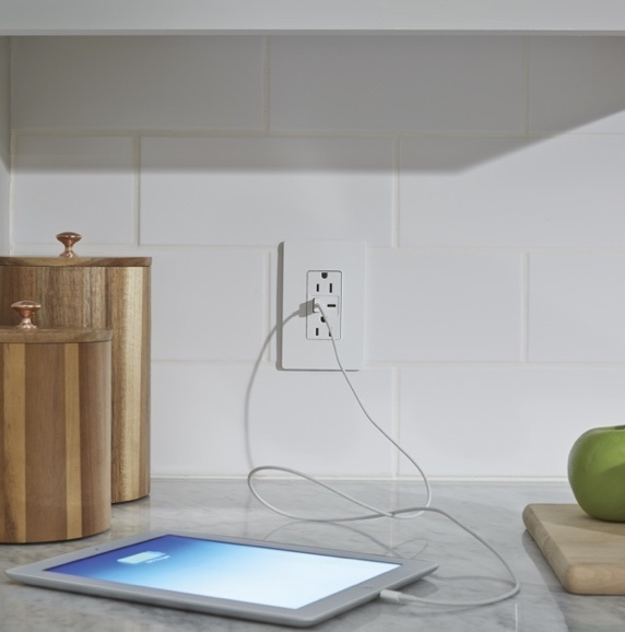 Legrand's radiant Collection USB-A/C outlet on white tiled kitchen back splash charging phone