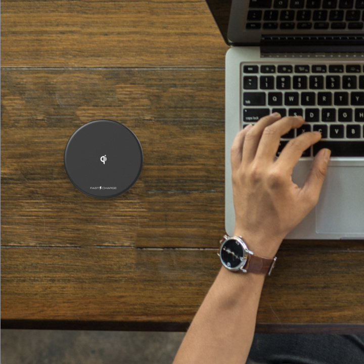 Wireless charging puck on table with laptop and hand