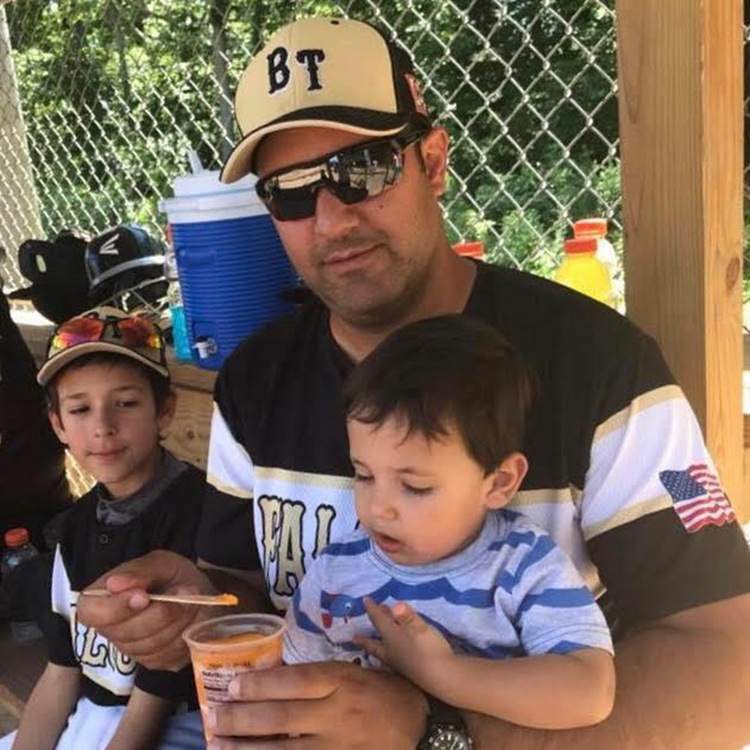 Vince Saba feeds young son while other son sits next to him