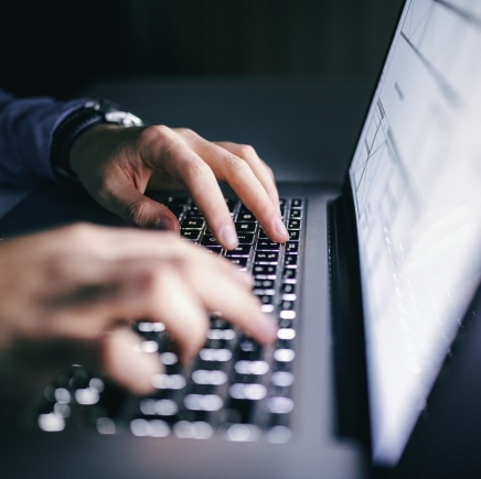 A guy typing on laptop with light up keyboard