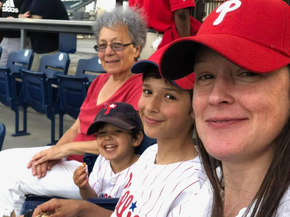 Saba's wife. two sons and mother sit in a row together at a Phillies baseball game
