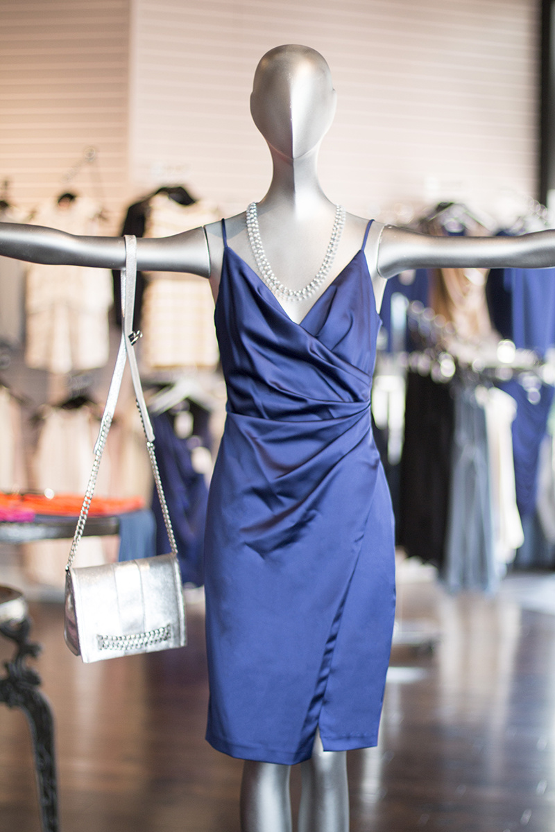 From Lori James: Indigo satin cami dress, $247; layered semi-precious stone necklace, $350; Silver chained crossbody/clutch bag, $395