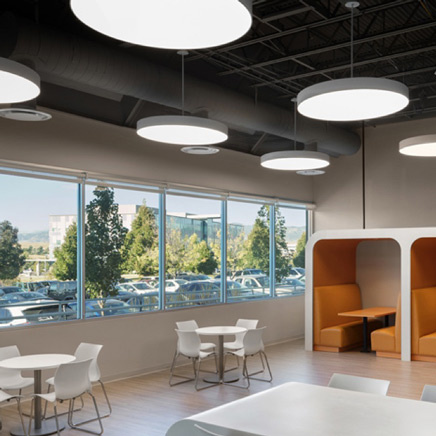 Pendant lights hanging in cafe with white tables and orange booths