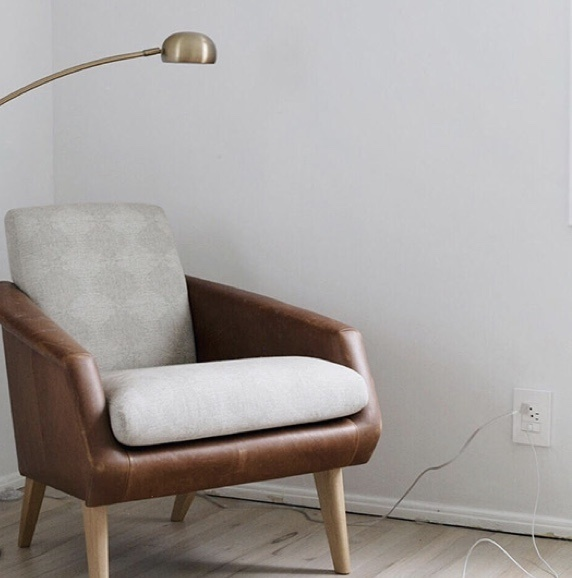 brown leather arm chair and gold lamp next to adorne Collection standard outlet in white paired with half-size USB outlet
