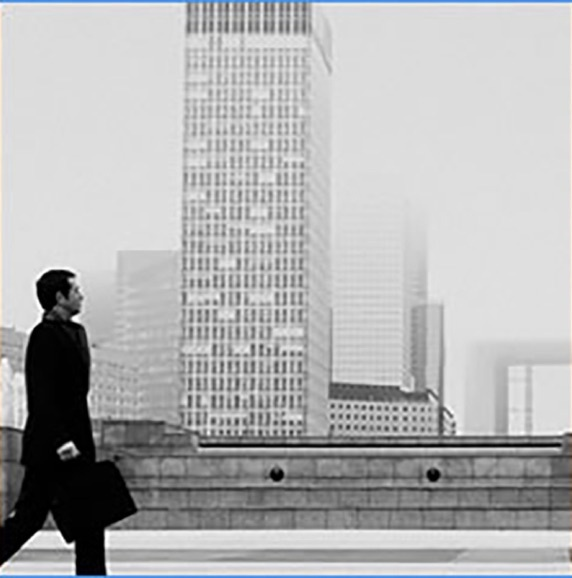 Man walking to work with skyscraper in the background in black and white photo