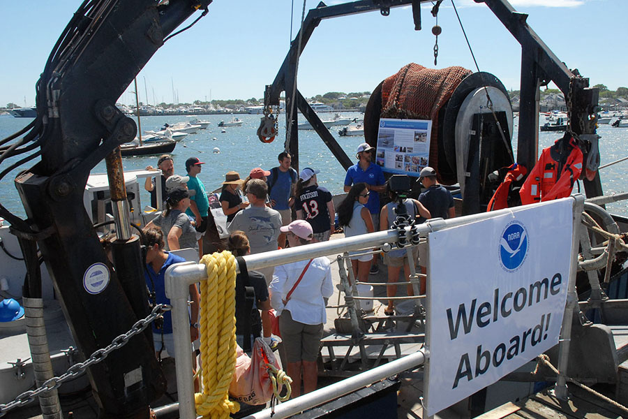 visitors crowding around vessel's fantail
