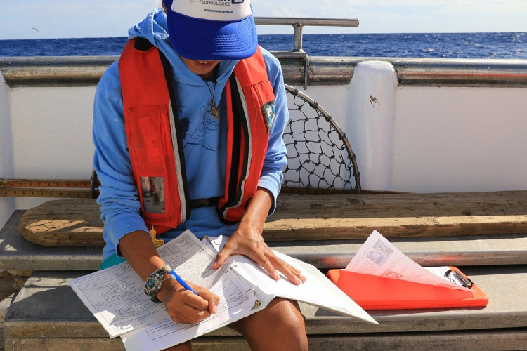 Holly Ann Naholowaa, trained fishery observers recording data on a U.S. commercial fishing vessel.