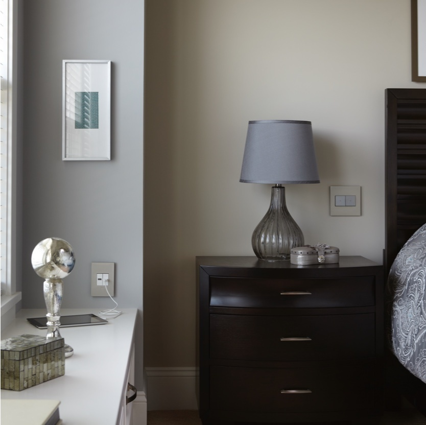 bedroom with dark wood nightstand and lamp