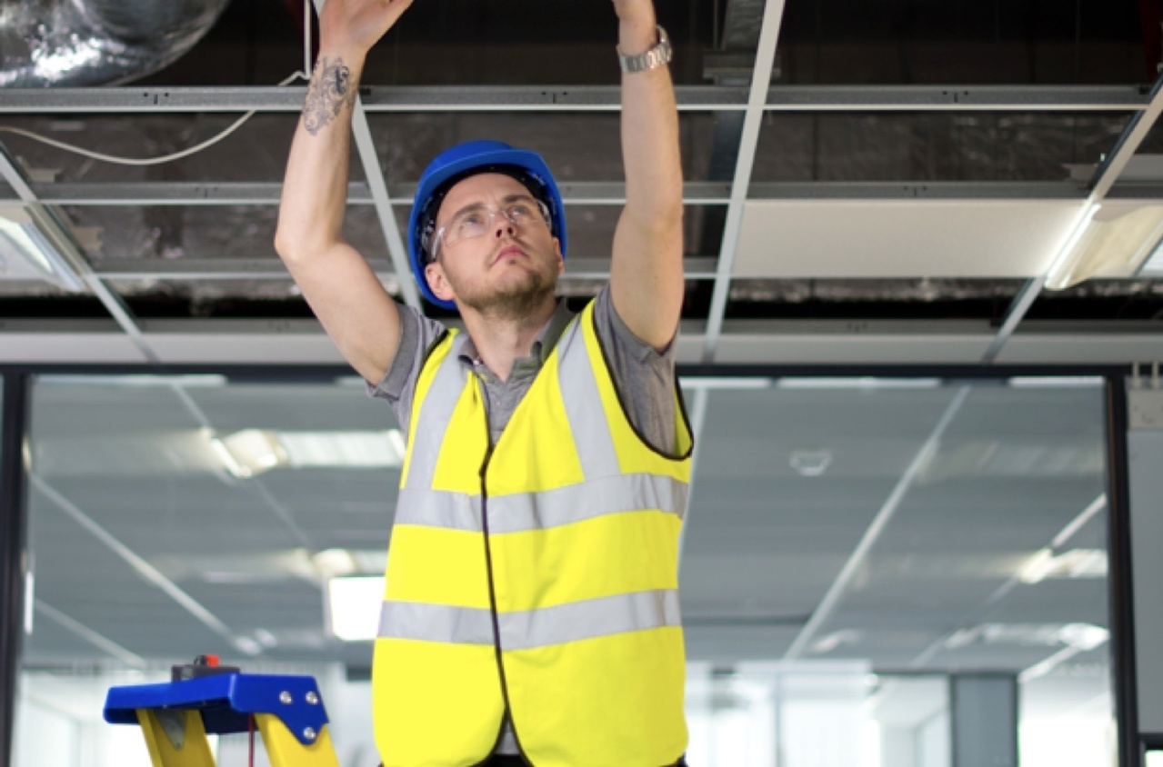 Man in a yellow vest and blue hard hat standing on a ladder installing facility lighting into the ceiling of a healthcare facility