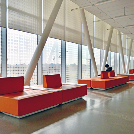 Four orange lobby seats against the wall of windows at Centennial Colleg