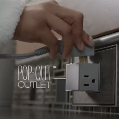 Woman plugging in cord to pop-out outlet