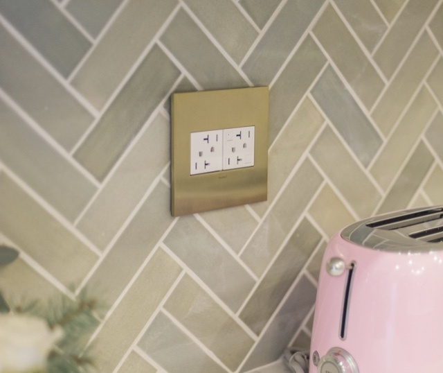 adorne Collection by Legrand white GFCI outlet with brass wall plate in stone kitchen backsplash