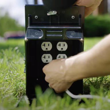 hand plugging in outlet of outdoor ground box in ground