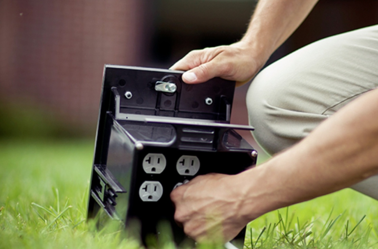 Person plugging a cord into an outdoor power source