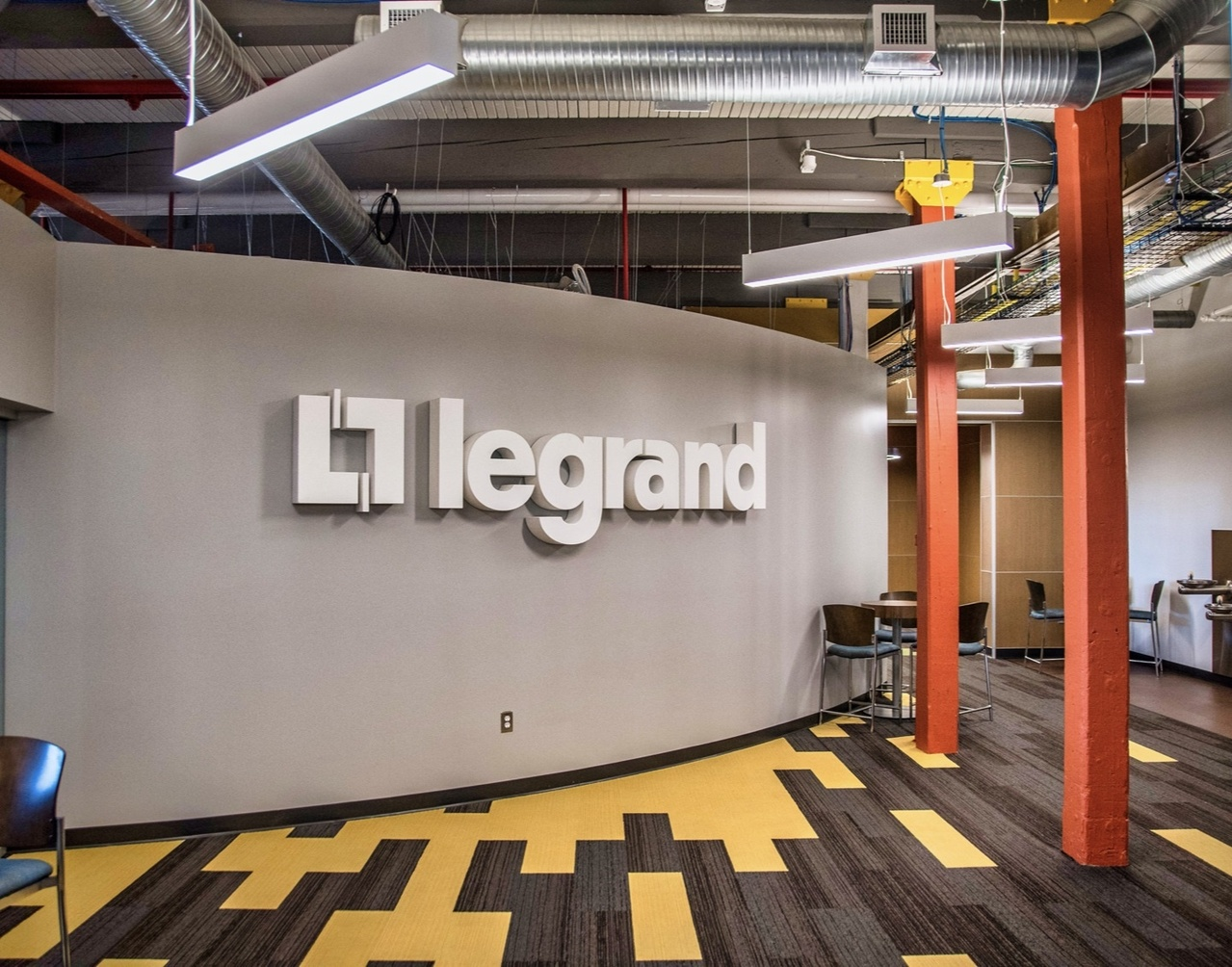 Gray wall with the Legrand Logo in white