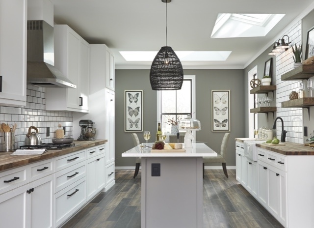 kitchen with white cabinets and wooden counter tops with large island in the center