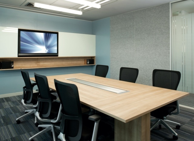 Conference room table and chairs with a tv mounted on the wall