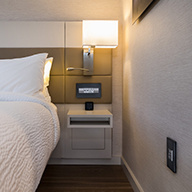 Floating bedside table in hotel with in wall lamp