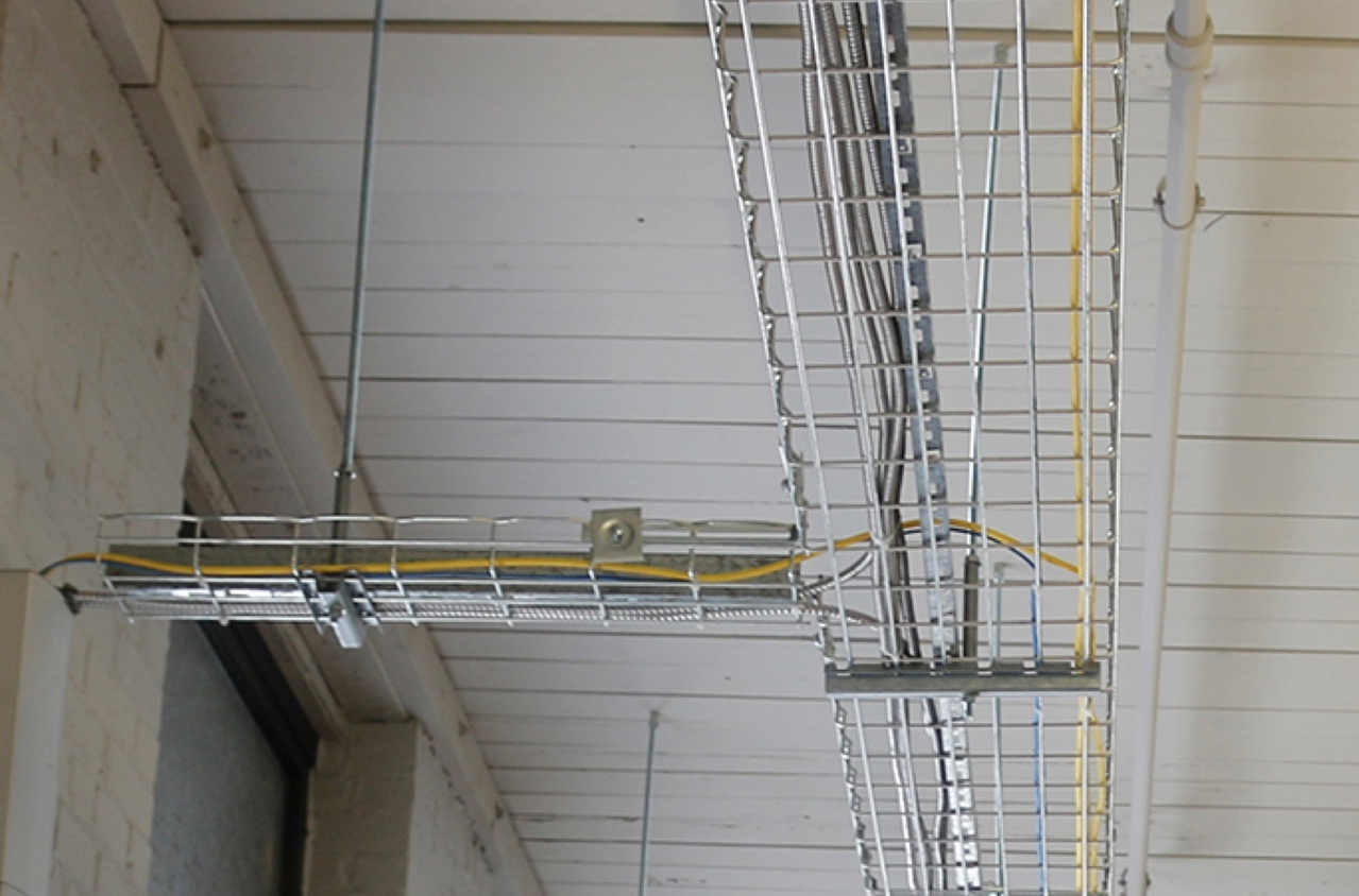 Wire mesh cable tray suspended from white ceiling