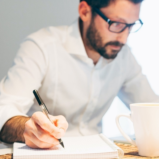Man in glasses with white shirt writing on graph paper with white coffee mug