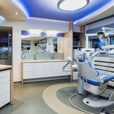 Dentist office with blue chairs and white cabinets