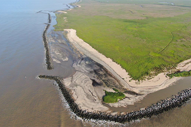 Aerial view of coastline and breakwater