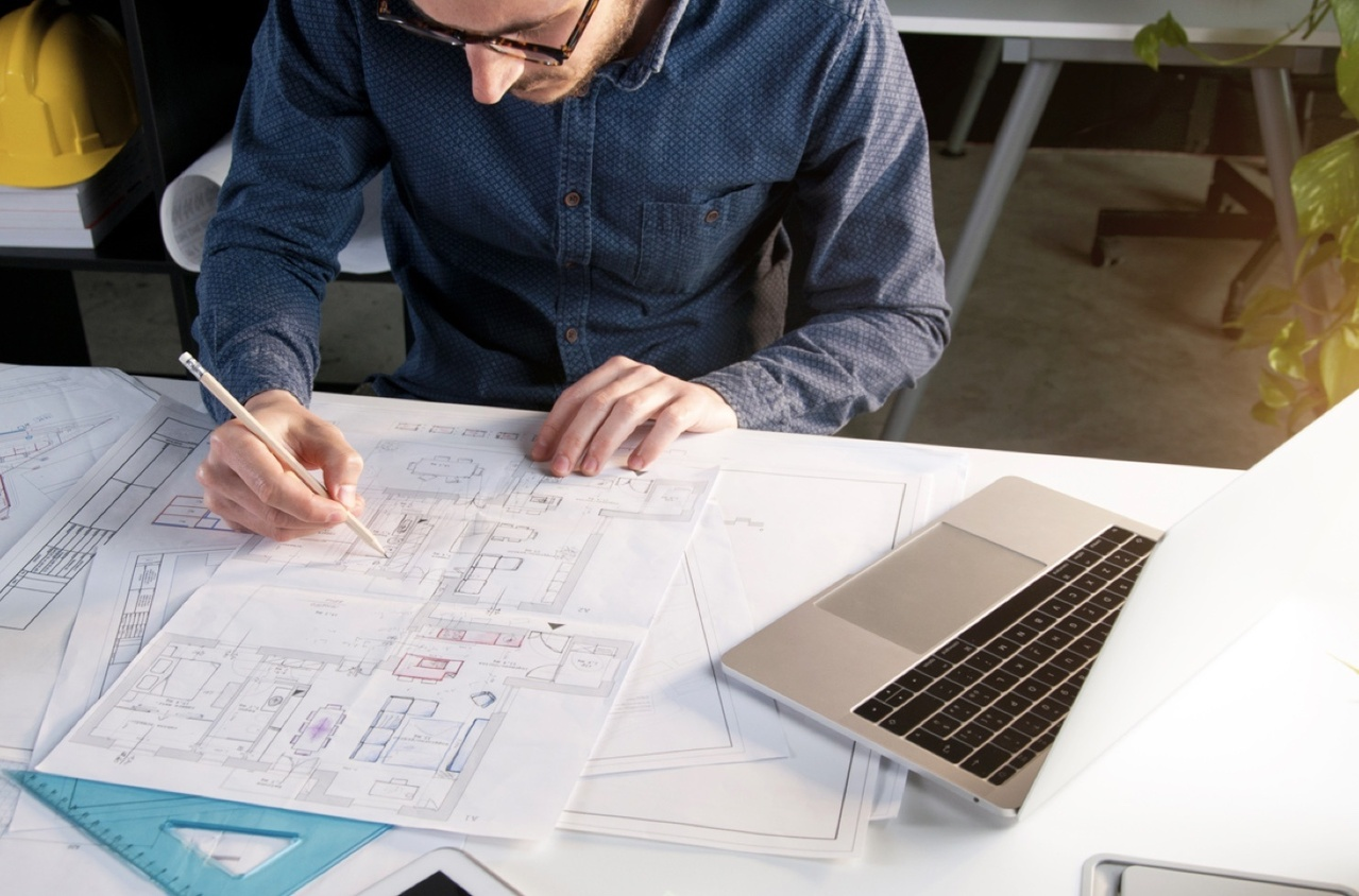 Man sitting at a desk drawing floorplans