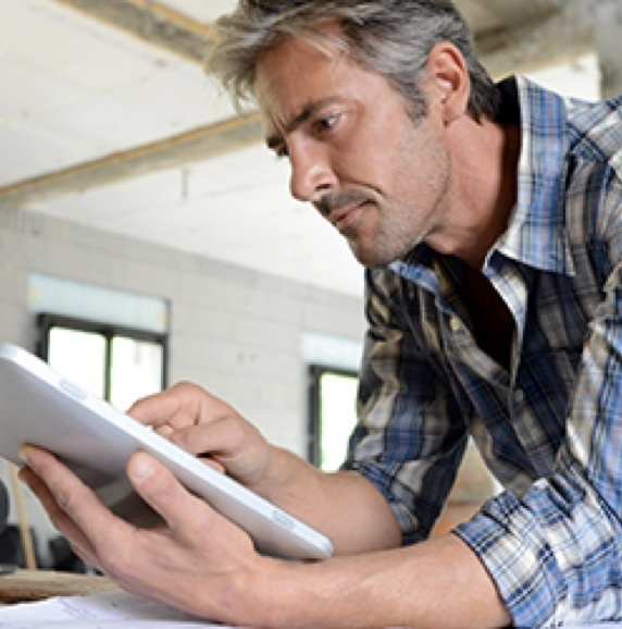 man in plaid shirt leaning over while reading instruction manual in his home