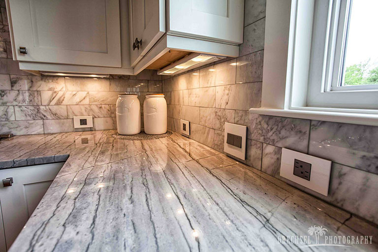 adorne white wall plates, outlets, and switches in kitchen with white marble counters