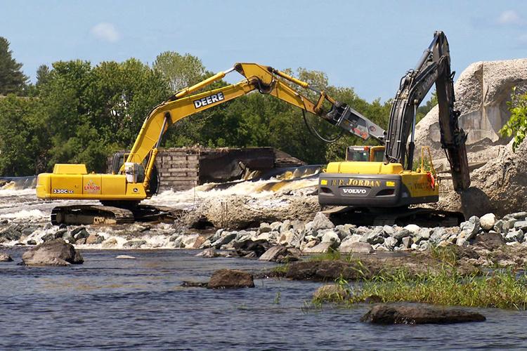 Heavy machinery demolishing a dam