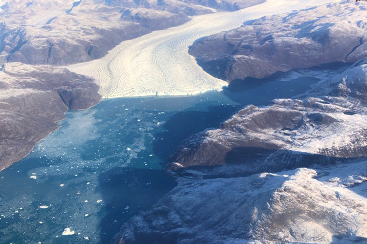 Greenland ice sheet migrates down a valley and spills into a fjord along the west coast of Greenland.