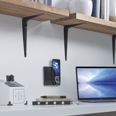 white desk with laptop, wireless charger, and wooden shelves