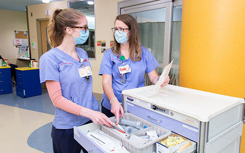 Nurses chatting at cart