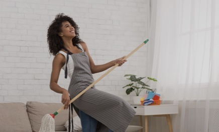 Woman dancing in her living room while cleaning with a broom in her hand