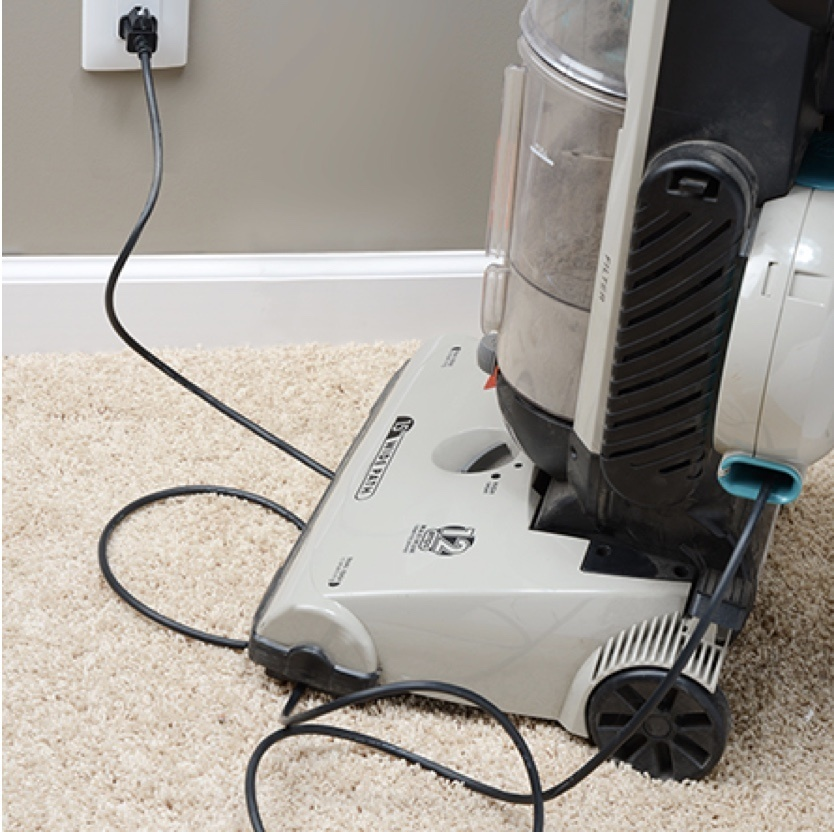 vacuum cleaner running over cord on beige carpeting