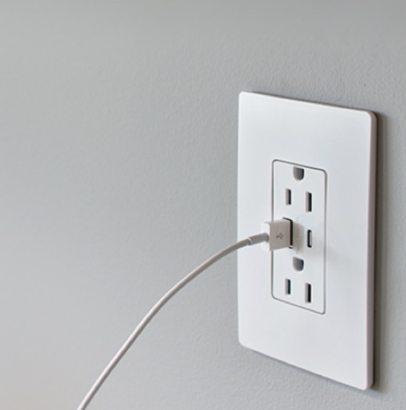 PlugTail USB Charging receptacle on a gray wall with a charger plugged in