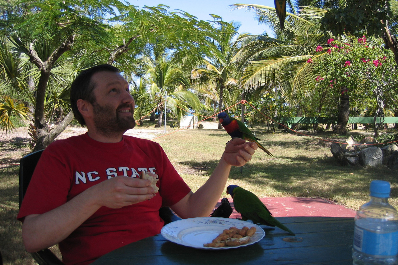 Harvey seated at a table eating lunch and holding one bird, is joined by a few other colorful birds on Great Keppel Island, Australia
