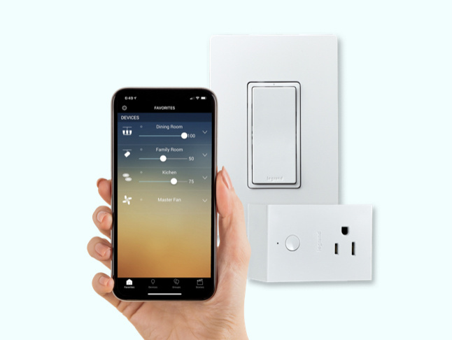 hand holding smart phone next to smart light switch and plug-in outlet and dimmer