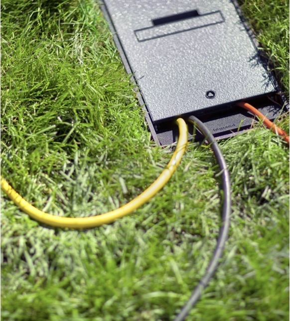 Overhead view of outdoor ground box installed in grass with cords running from opening