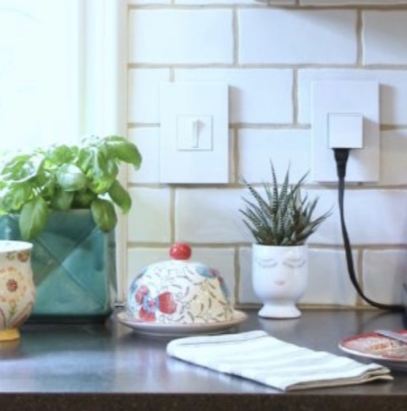 White wireless charger against white tile with wood and greenery accents
