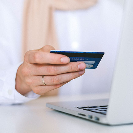 Someone shopping online and holding their credit card in their hand