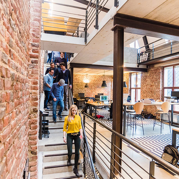 Office workers using staircase in modern commercial space with brick walls and beams