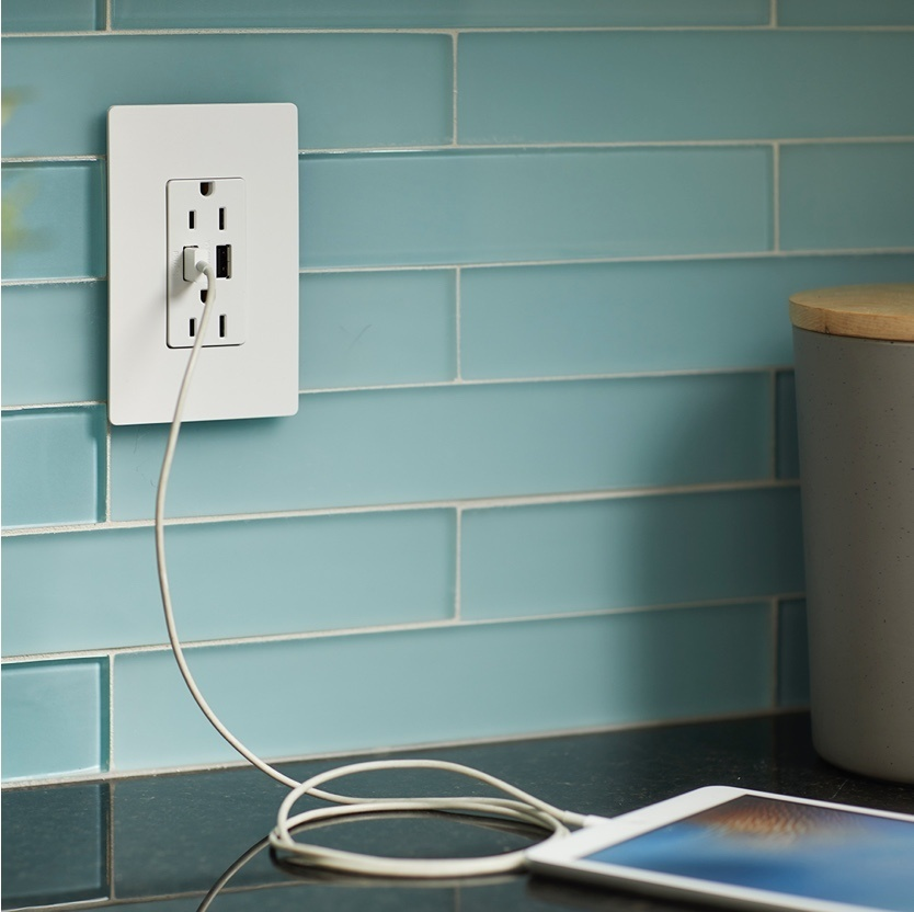 White outlet with two USB charging ports charging a tablet in kitchen with teal backsplash