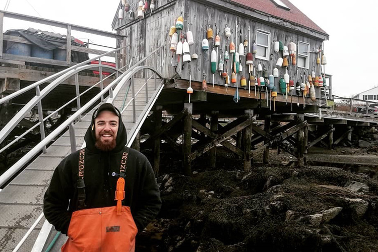 Zach Fyke stands on dock near walkway up to shed decorated with fishing floats.
