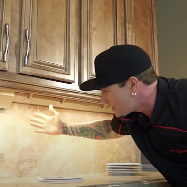 Vanilla Ice in his kitchen showing the underneath of his cabinets