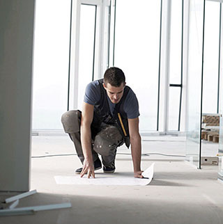 Professional architect laying out a floor plan on the floor of his workspace