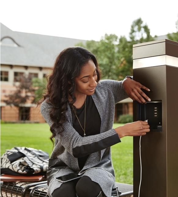 Mobile image of a woman using an Outdoor Charging Station to charge her device