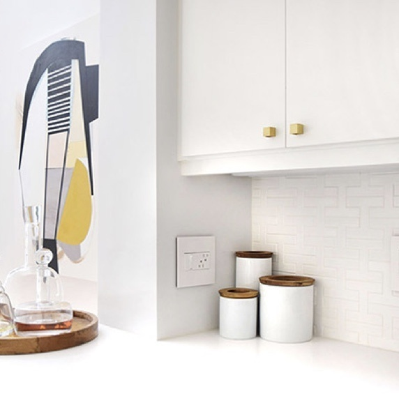 Clean white kitchen with white outlet, white cabinets, white counters