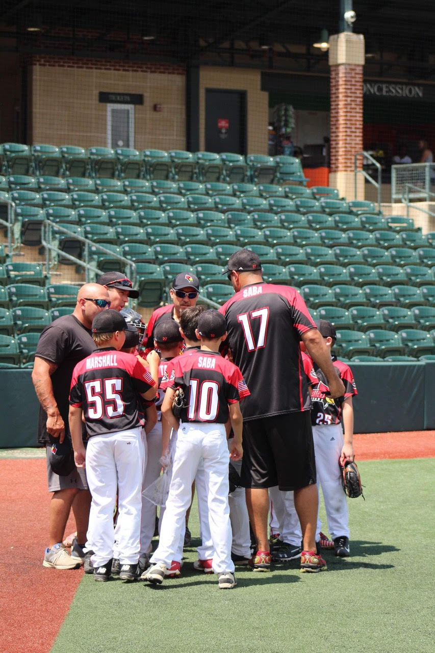 Saba with son and youth baseball team stand in a huddle at a baseball field